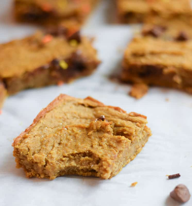 Freshly baked healthy pumpkin bars with a bite taken out on parchment paper