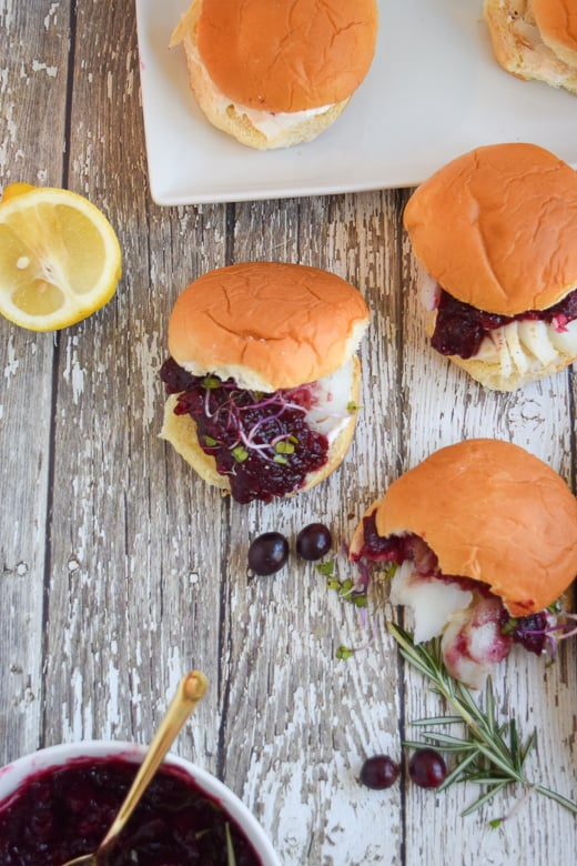 Holiday slider appetizers topped with cranberry sauce on wooden background