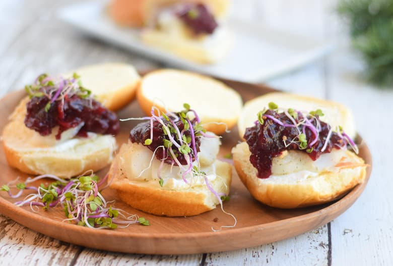 Alaska cod sliders with cranberry churney on brown serving board topped with sprouts