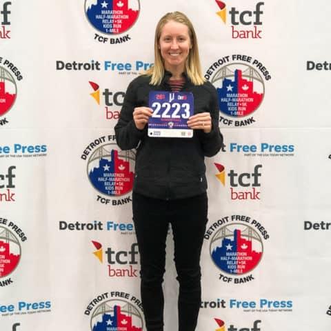 girl holding Detroit Marathon bib in front of background