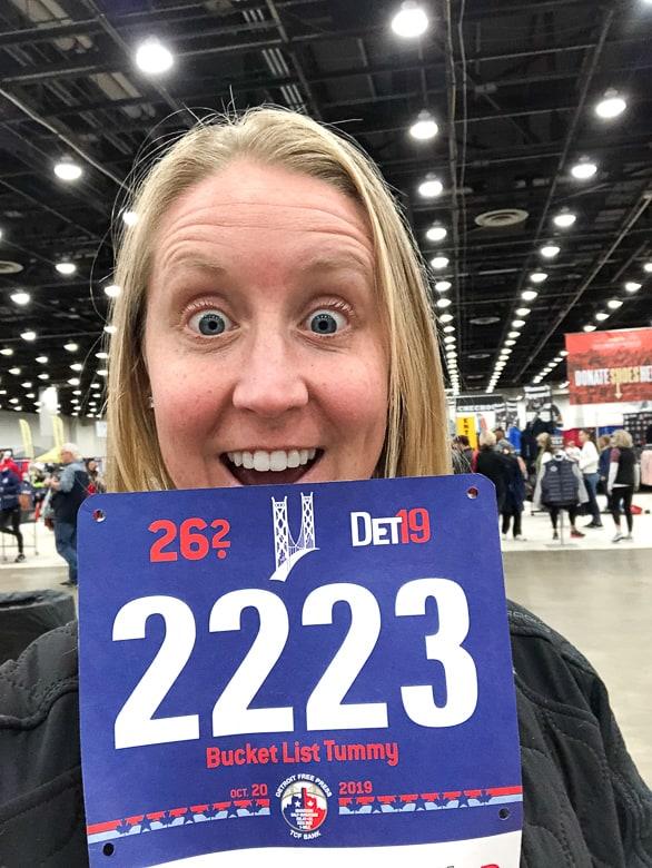 girl holding Detroit Marathon bib for 2019