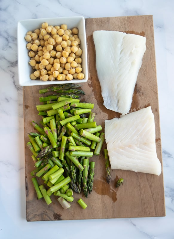 Alaskan halibut with chopped asparagus and chickpeas on cutting board