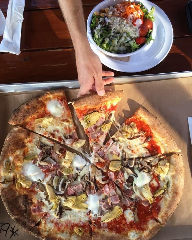 Person grabbing piece of pizza