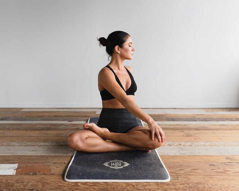 woman twisting and stretching on yoga mat