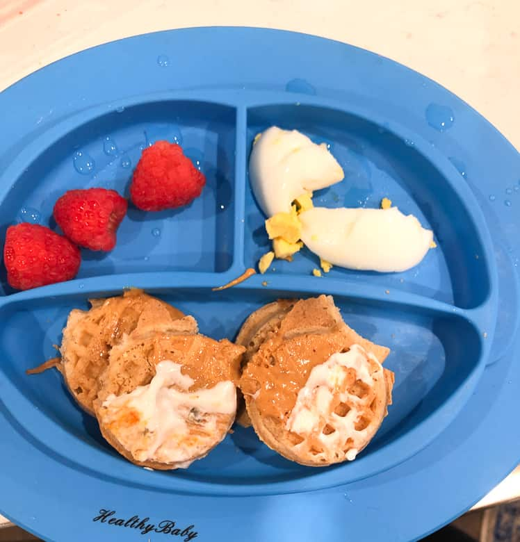 Toddler breakfast plate with mini waffles, berries and eggs