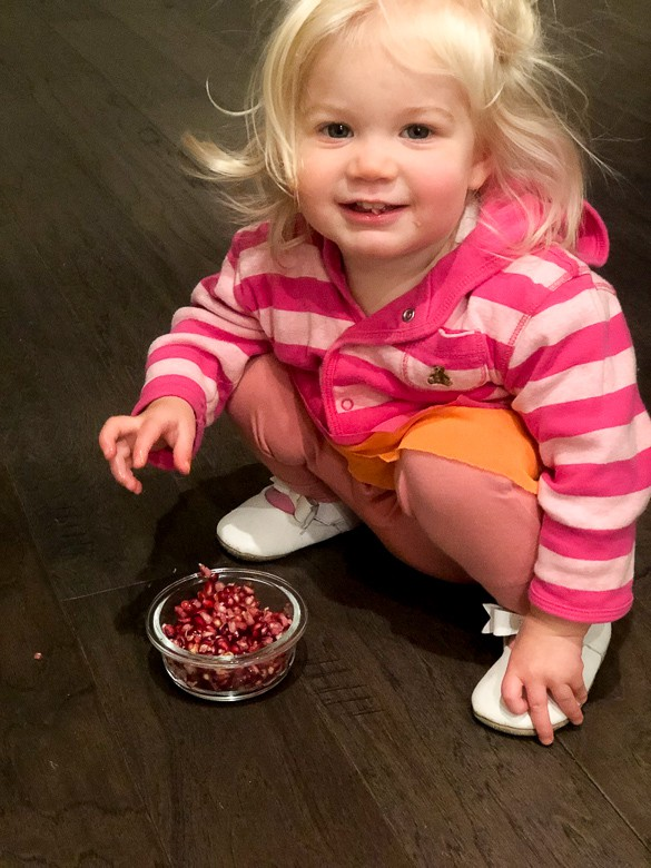 Toddler eating pomegranate seeds