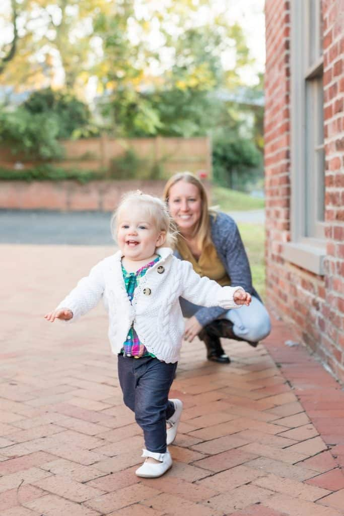 Toddler smiling and running away from mom