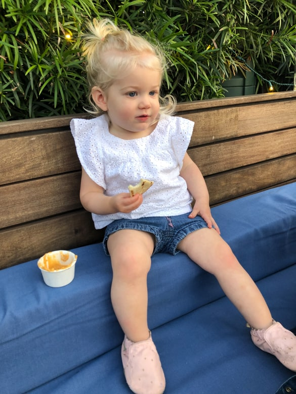 Toddler eating a snack on a bench