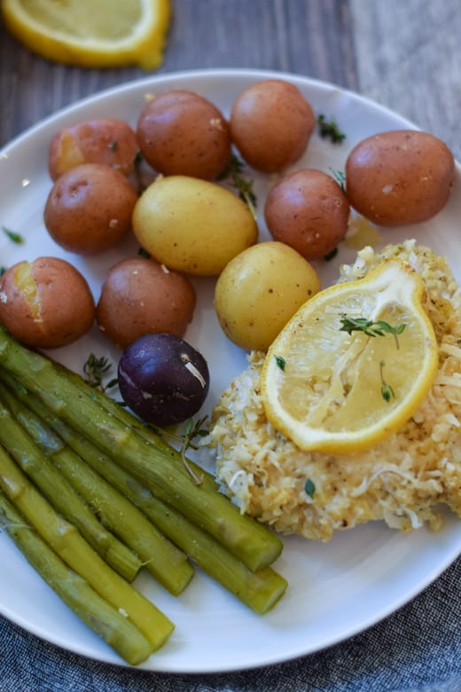 Coconut crusted fish with asparagus and baby potatoes on white plate