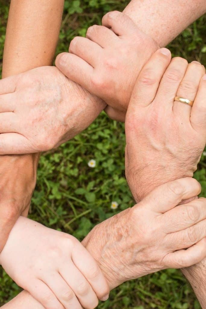 People holding wrists for support group