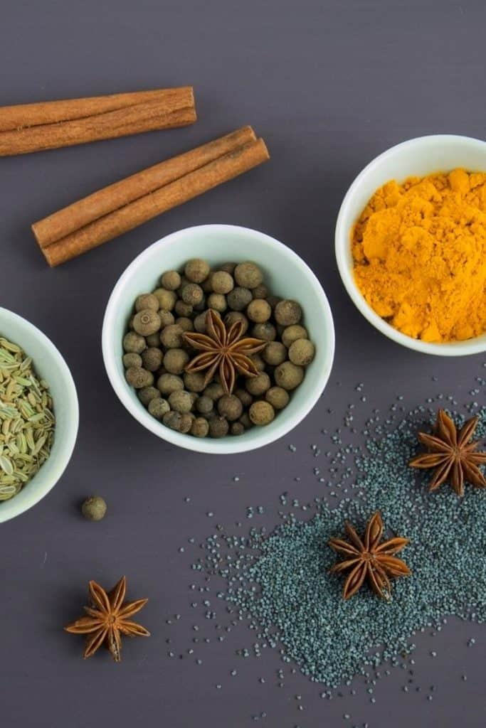 variety of spices in white bowls on dark countertop
