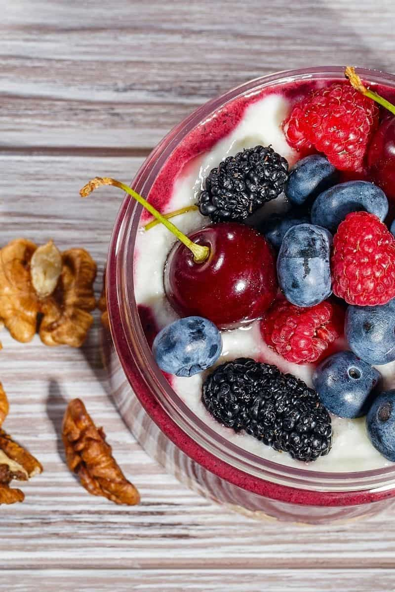 greek yogurt in serving bowl with berries and a cherry, with nuts on the side