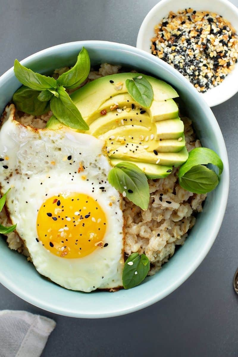 savory oatmeal topped with egg, herbs and avocado in white bowl.