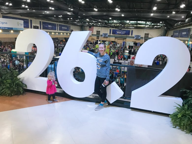 Girl in front of 26.2 sign at Disney Marathon Expo