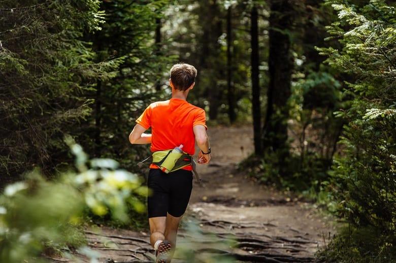 back male runner marathon runner running in forest. water bottle belt