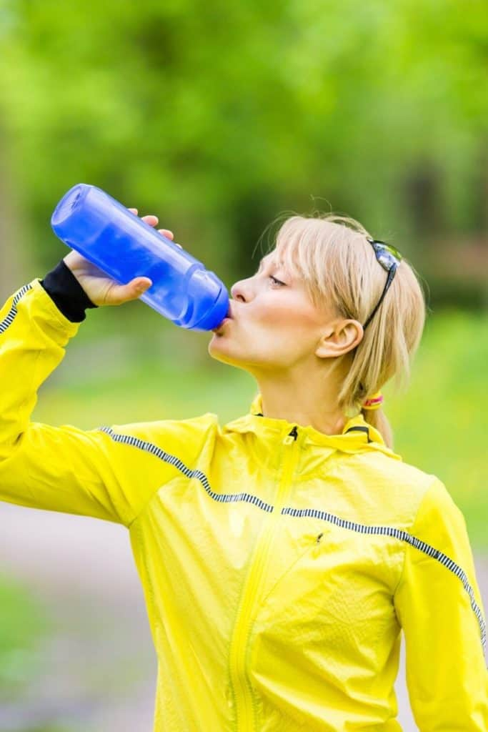 woman drinking water before running