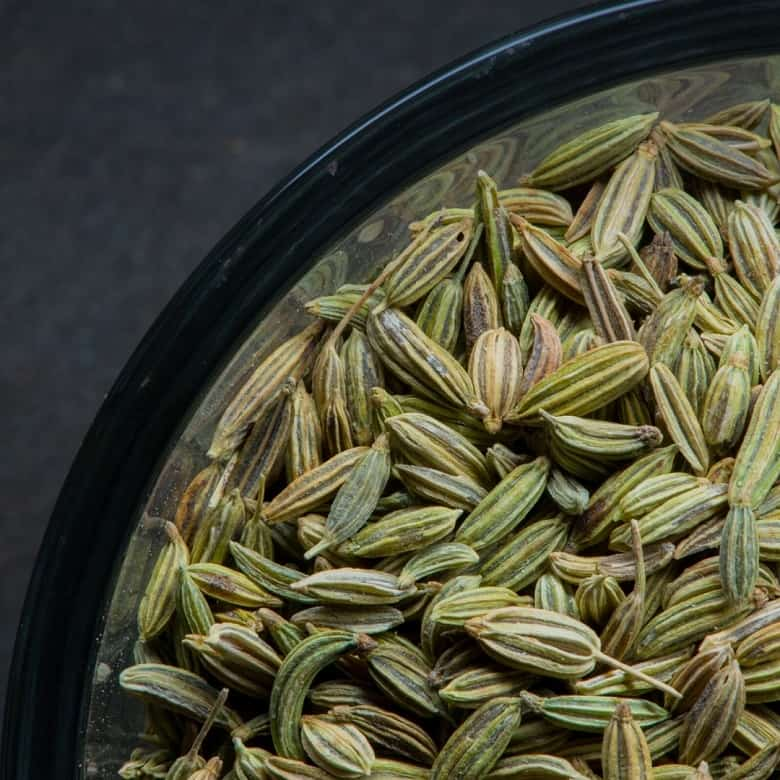 close up of fennel seeds in bowl over dark background