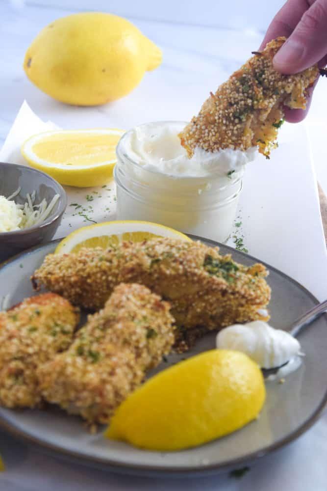 Dipping gluten free fish sticks into honey yogurt sauce