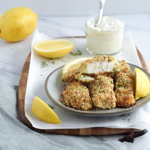 Homemade gluten free fish sticks on blue plate with lemons and side of honey yogurt dip | Bucket List Tummy