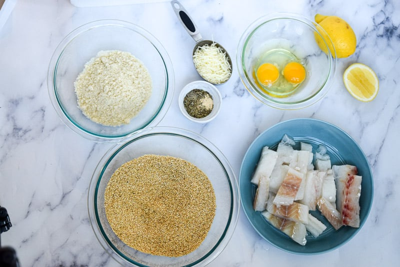 flour, quinoa, raw cod and eggs in separate bowls on granite countertop to use in recipe for gluten free fish sticks | Bucket List Tummy