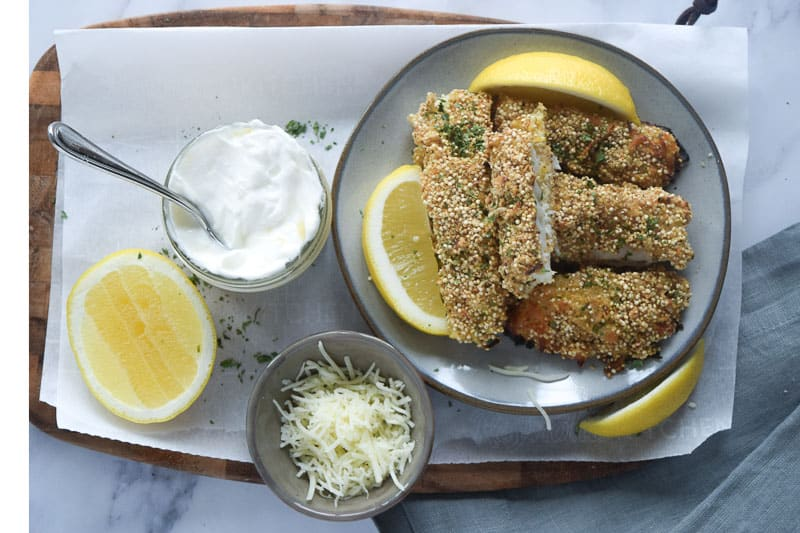 Healthy fish sticks with quinoa breading on small plate with lemons and side of yogurt dipping sauce | Bucket List Tummy