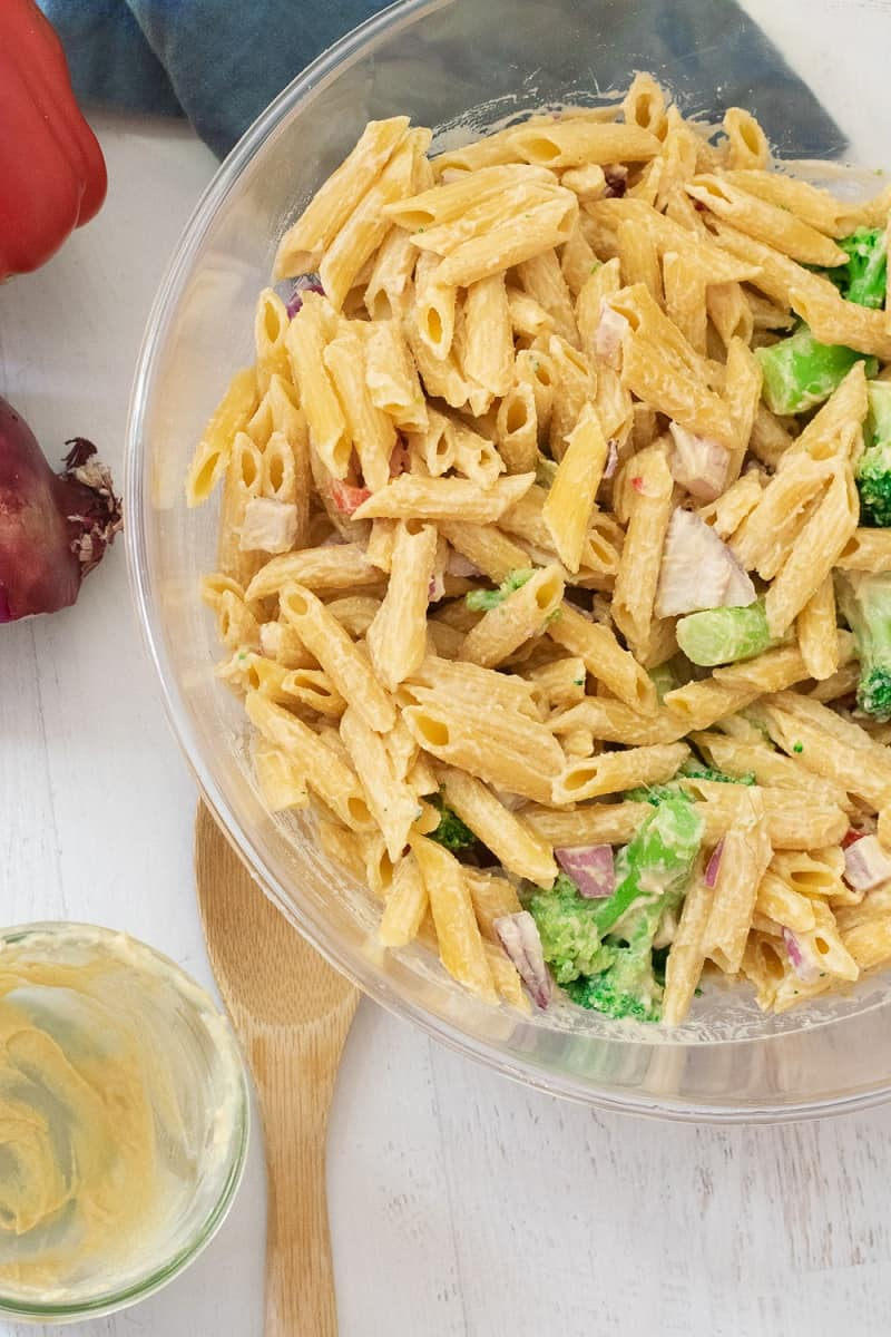gluten free pasta salad in clear bowl with vegetables and hummus pasta sauce dressing