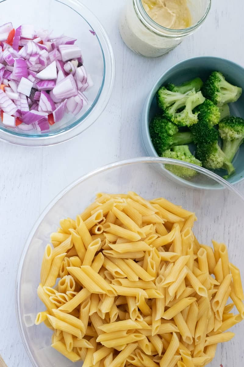 clear bowl with gluten free pasta, bowl of broccoli and bowl of onions and peppers