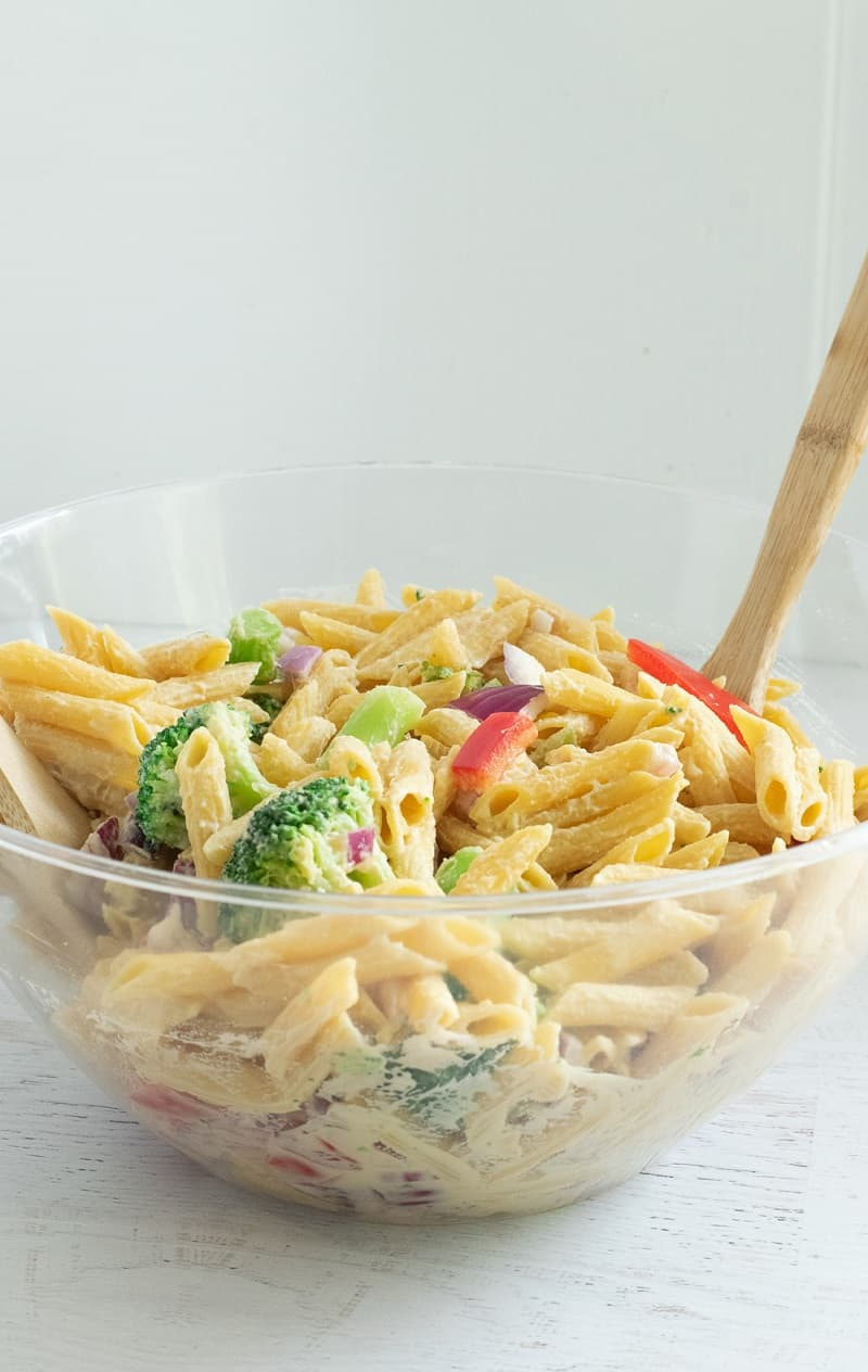 Hummus Pasta Salad in clear mixing bowl with wooden spoon