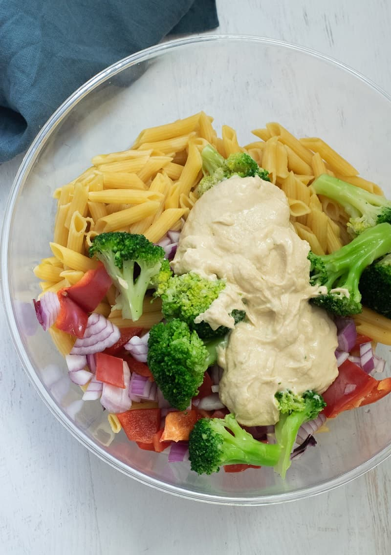 mixing bowl with pasta, hummus sauce and vegetables