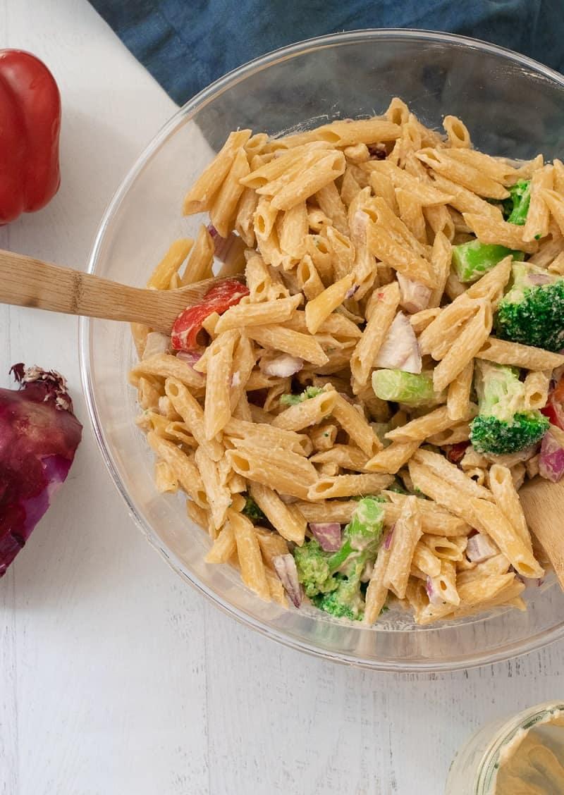vegan pasta salad in clear bowl with veggies and hummus dressing