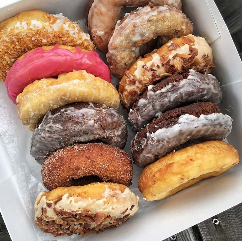 assortment of a dozen donuts in a to go box