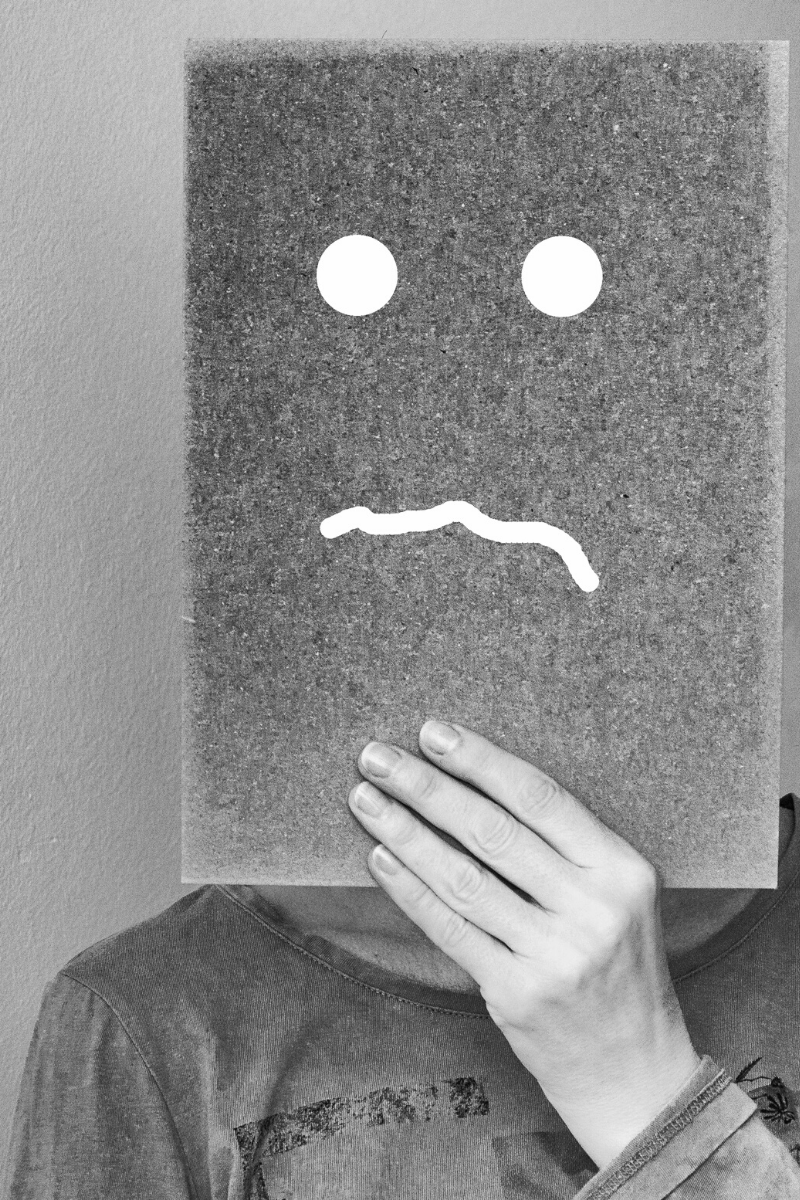man holding up question face