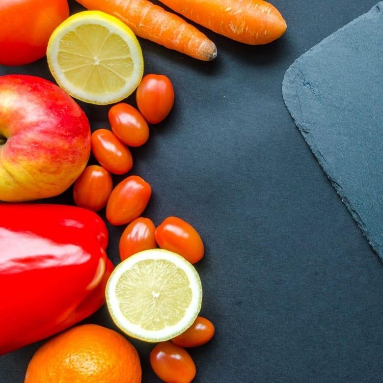 fresh produce next to black cutting board