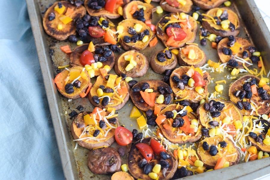 loaded sweet potato nachos on baking sheet with vegetarian toppings