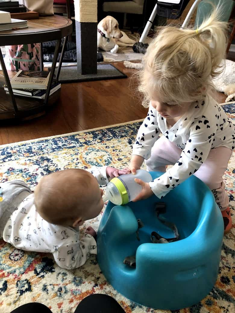 toddler feeding bottle to a baby