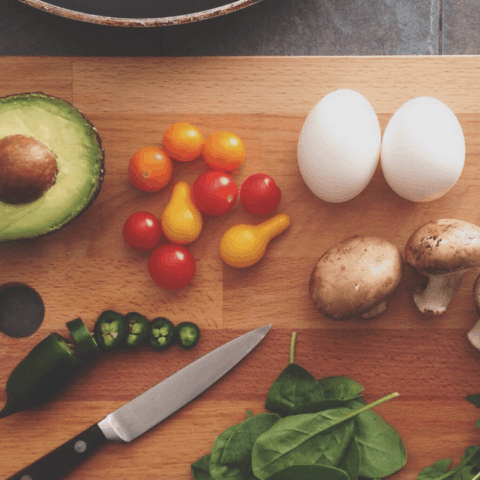 cutting board with eggs and vegetables for meal prep