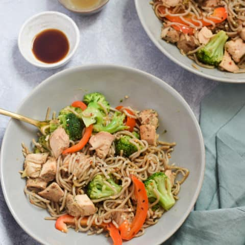 Overhead bowls of egg noodle stir fry with side of soy sauce
