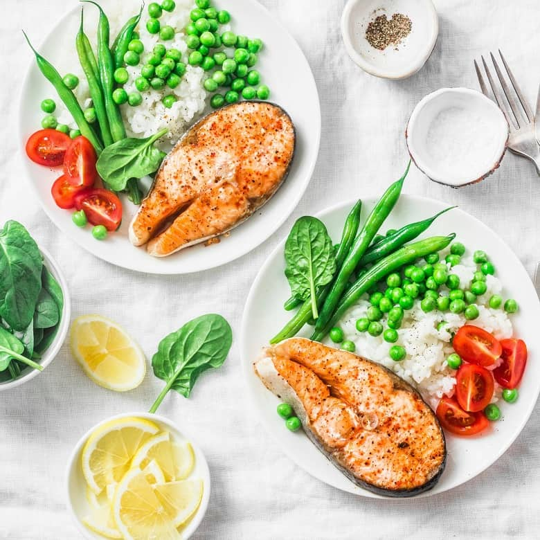 Two plates with fish, veggies and rice