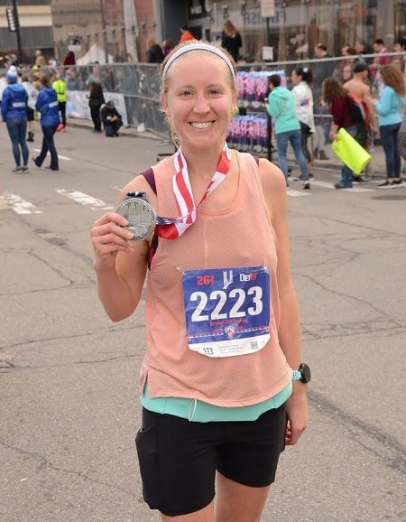 holding finisher's medal after detroit free press marathon