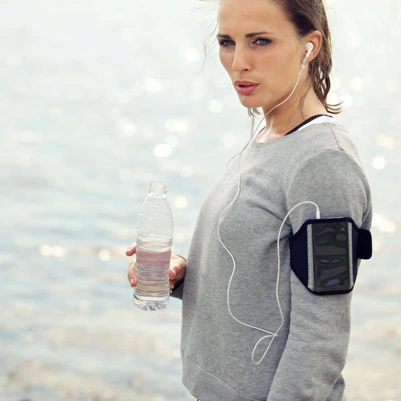 female runner drinking water in front of ocean