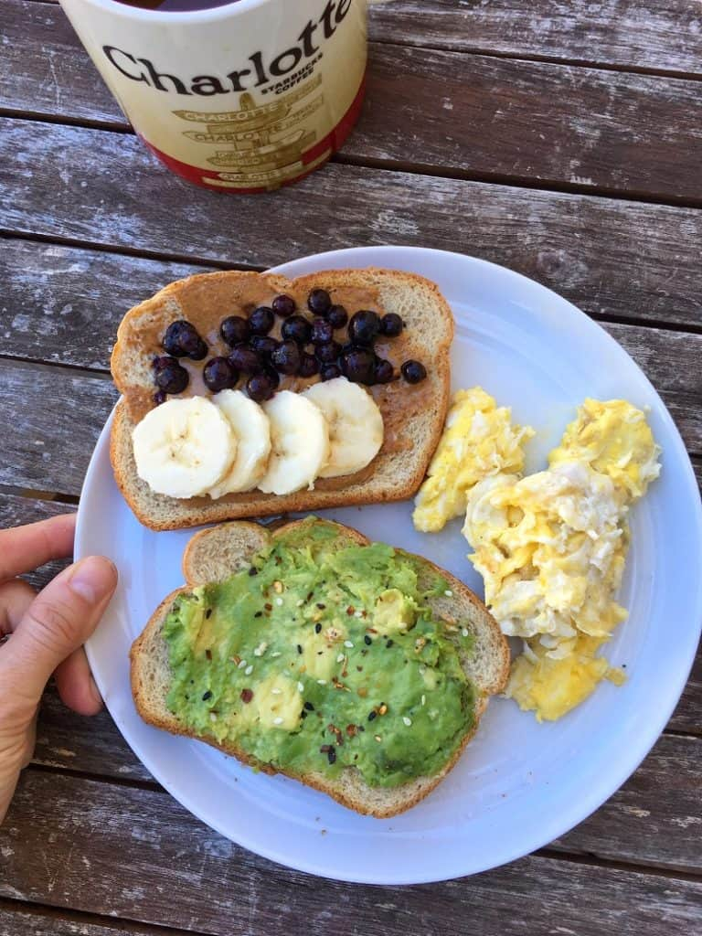 avocado and peanut butter toast with eggs on white plate for breakfast