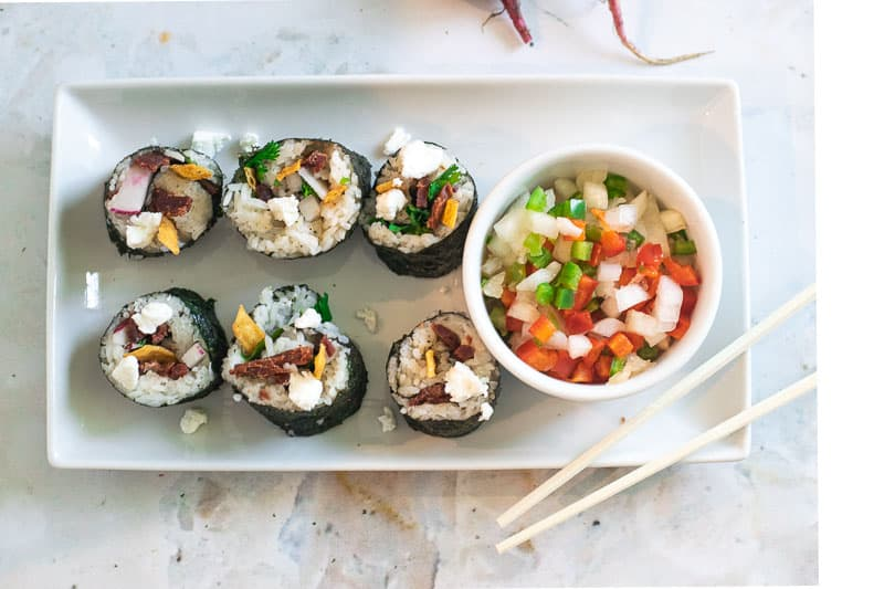 overhead photo of beef sushi on white plate with chopsticks and small bowl of pico de gallo