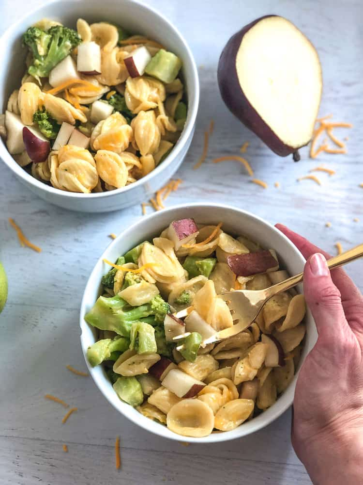 two white bowls with homemade mac and cheese with pears and broccoli