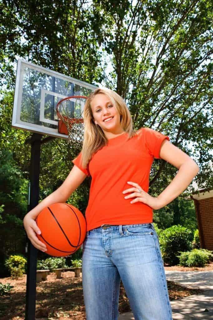 Girl holding basketball in front of basketball hoop