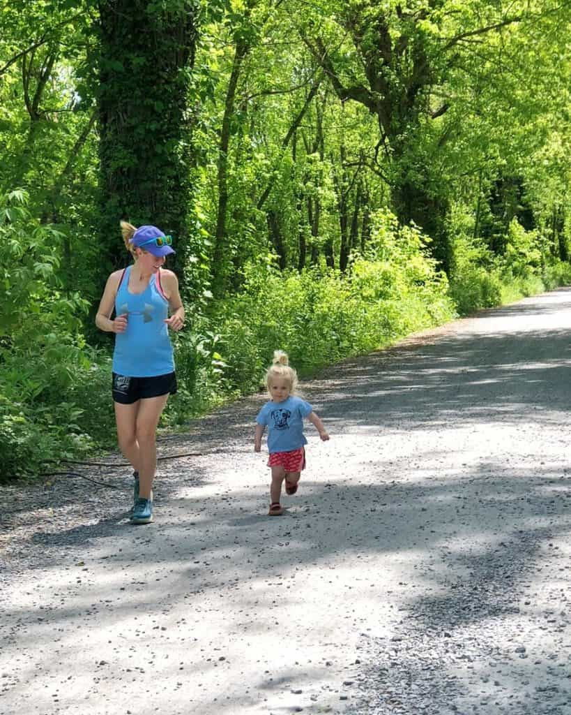 mom running on gravel path with daughter