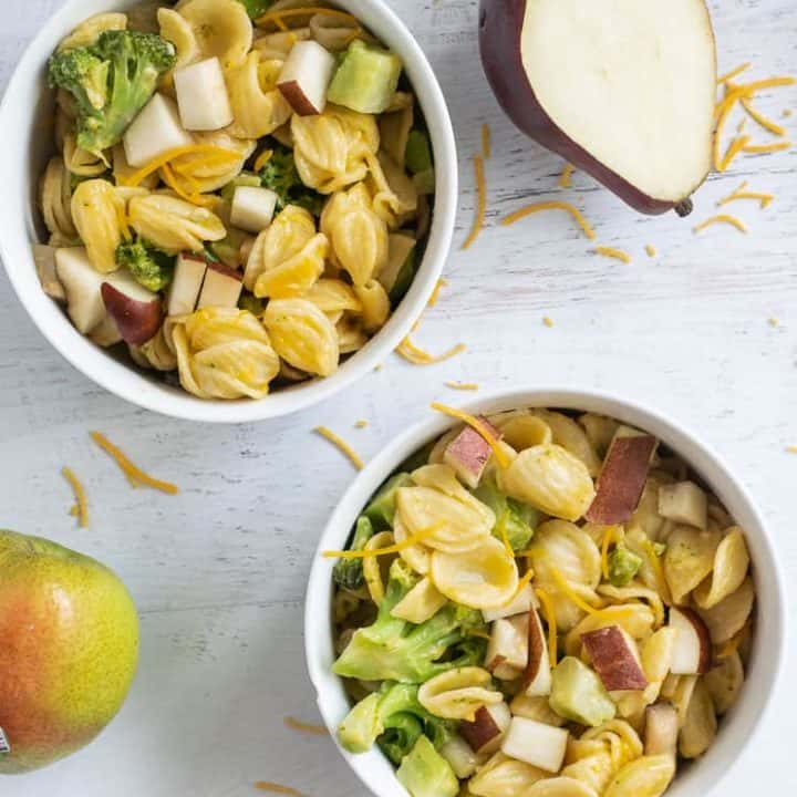 mac and cheese with pears and broccoli in two white bowls on white counter