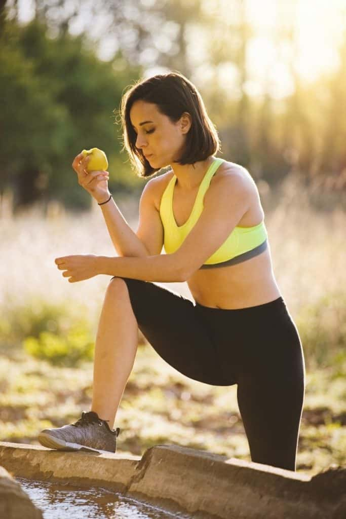 female runner stretching and eating apple