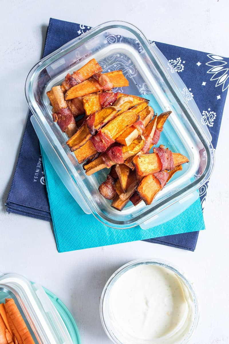sweet potato wedges in clear tupperware on blue napkin with side of greek yogurt dip