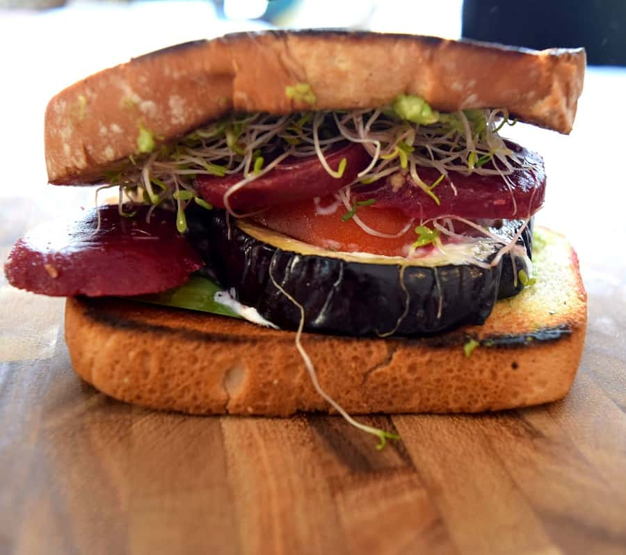 eggplant, tomatoes and sprouts on a sandwich on wooden cutting board