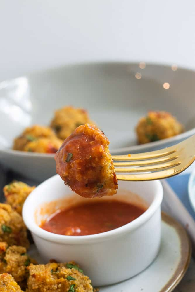 Dipping quinoa meatballs in ramekin of marinara sauce
